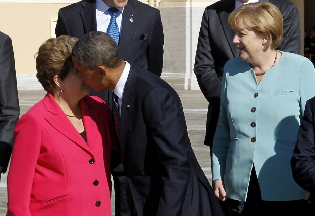O presidente Barak Obama beija a presidente Dilma Rousseff observado pela chanceler alemã Angela MerkelKote Rodrigo/EFe